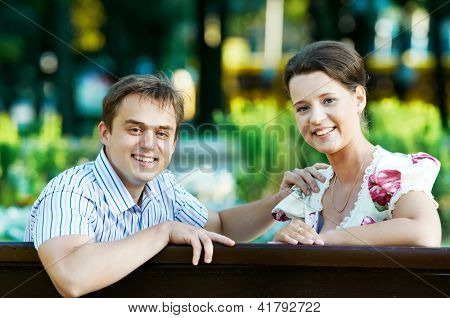 Two Smiling young attractive people sitting on bench in spring park