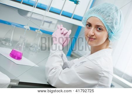 Portrait of woman medic scientific researcher or pharmacy doctor with flask pink liquid solution and medicine dropper