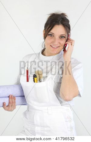 Female decorator holding rolls of wallpaper whilst making telephone call