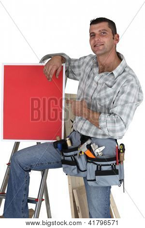 Carpenter posing with red poster