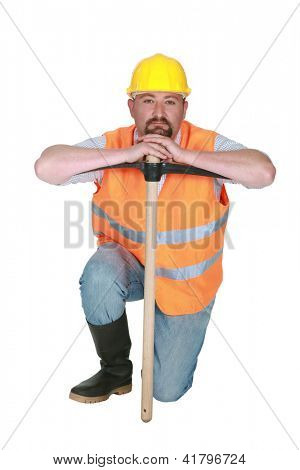 Construction worker leaning on a pickaxe