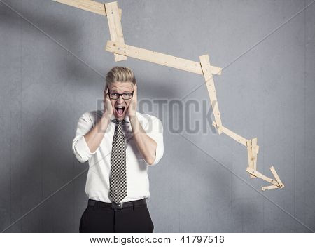Concept: Business crash. Young stressed businessman shouting in front of business graph with negative trend, isolated on grey background.