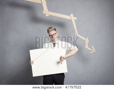 Concept: Business decline. Displeased businessman giving thumbs down at white empty signboard with space for text in front of business graph with negative trend, isolated on grey background.
