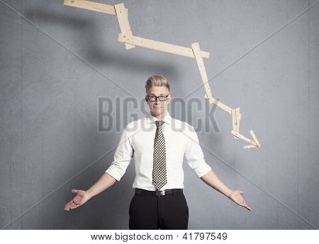 Concept: Business decline. Young displeased businessman in front of business graph pointing down, isolated on grey background.