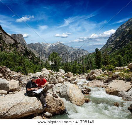 Hiker trekkers read a trekking map on trek in Himalayas mountains. Himachal Pradesh,India