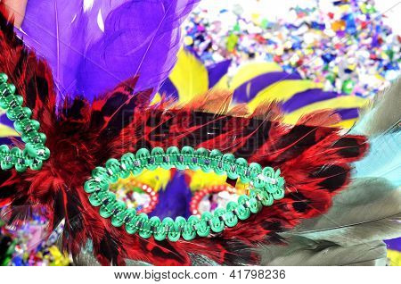 a carnival mask with feathers of different colors on a background with confetti