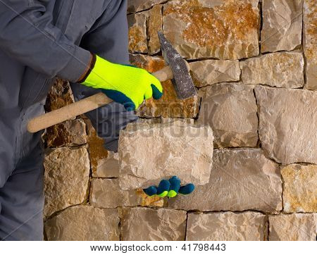 stonecutter mason with hammer and stone building a masonry stone wall