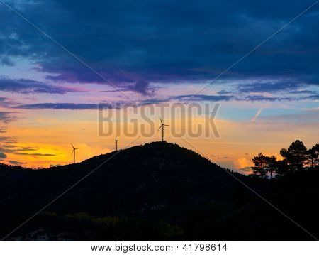 Sunset mountain with electric windmills aerogenerators backlight