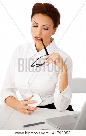 Attractive businesswoman with glasses in her hand sitting looking with downcast eyes at something on the screen of her laptop against a white background