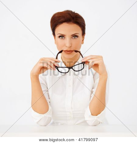 Beautiful businesswoman holding a pair of glasses in her hands as she looks at the camera with a serious expression on a white background