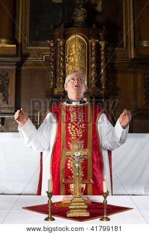 Catholic priest saying a prayer during mass in a medieval church with 17th century interior (including the painting)