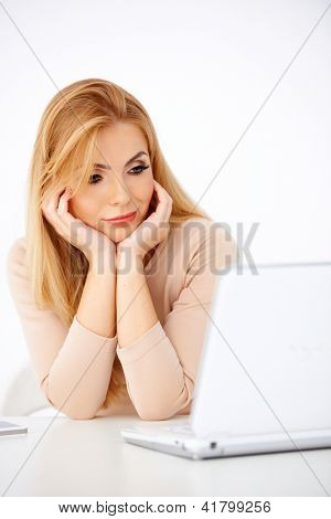 Attractive young blonde woman looking worried at her laptop