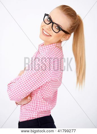 Pretty girl, smiling and looking at camera, wearing black framed glasses. Side view. White background