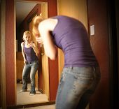 stock photo of grief  - A young woman is depressed looking in a mirror while the reflection is yelling an pointing at her self in anger - JPG