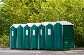 picture of porta-potties  - Green plastic toilet booths in park   horizontal photo - JPG