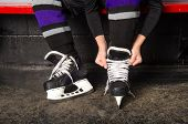 stock photo of hockey arena  - A child ties hockey skates in arena dressing room - JPG
