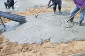 stock photo of work boots  - Concrete pouring during commercial concreting floors of buildings in construction - JPG