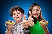 Kids eating healthy sandwiches on blue background