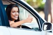 carefree woman in car driving with smile and confidence