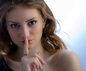 stock photo of shh  - portrait of attractive teenage girl with finger on lips - JPG