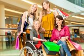 picture of four-wheel  - Four female friends with shopping bags having fun while shopping in a mall - JPG