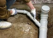 stock photo of sewage  - Plumber assembling pvc sewage pipes - JPG