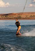 Brunette Girl Wakboarding At Sunset