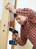 stock photo of locksmith  - Male handyman carpenter at interior wood door lock installation - JPG