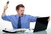 picture of crazy face  - Executive about to smash his laptop with a hammer - JPG