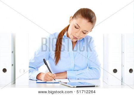 Efficient businesswoman working at her desk sitting writing notes from a tablet computer surrounded by neat rows of office files