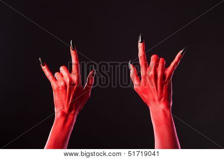 Red devil hands showing heavy metal, Halloween or music theme