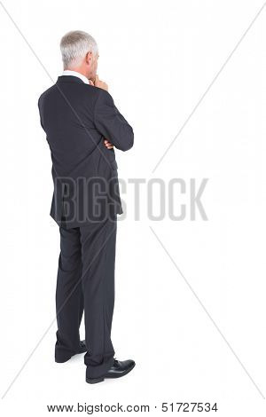 Thoughtful businessman standing back to camera on white background