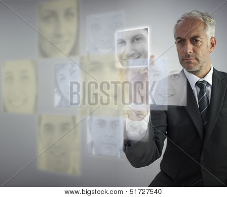 Stern human resources director selecting future employees on digital screen