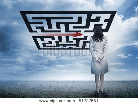 Businesswoman standing looking at arrow through qr code in cloudy desert setting