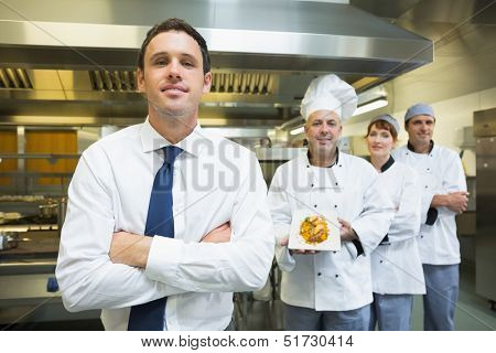Young restaurant manager posing in front of team of chefs smiling at camera