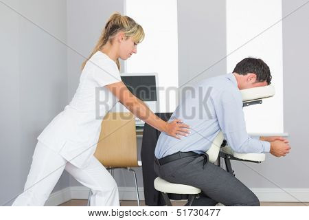 Masseuse treating clients lower back in massage chair in bright room