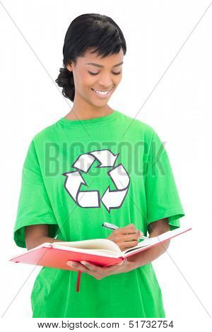 Happy black haired ecologist writing on an agenda on white background