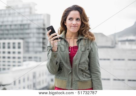 Skeptic gorgeous brunette in winter fashion holding smartphone on urban background