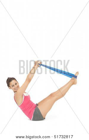 Cheerful sporty brunette exercising with resistance band on white background