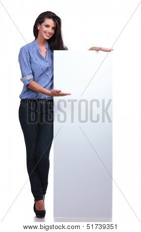 full length picture of a young casual woman presenting a blank pannel and smiling for the camera. on white background