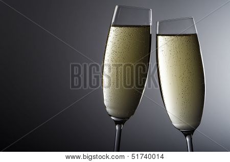 Two Champagne Glasses Before Grey Background