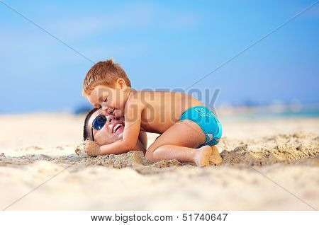 Happy Kid Gently Hugging Father's Head In Sand On The Beach