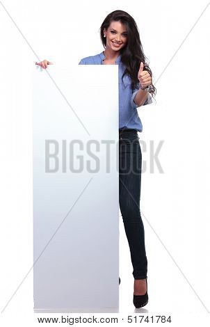 full length picture of young casual woman holding a big empty pannel and showing thumb up to the camera while smiling. on white background