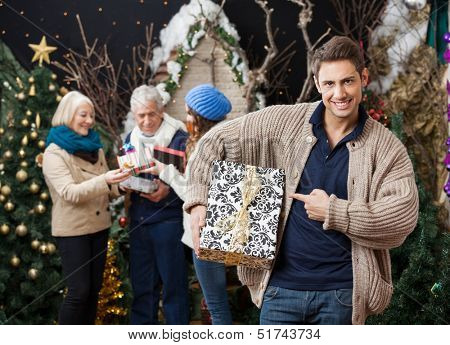 Portrait of happy young man pointing at Christmas present with family standing in background at store