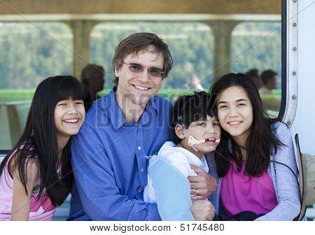 Father With His Biracial Children, Holding Disabled Son On Ferry Boat Deck