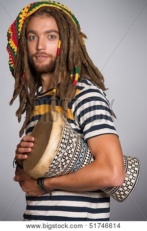 Portrait of a rastafarian guy playing his drum.