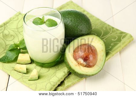 Fresh avocado smoothie on wooden background