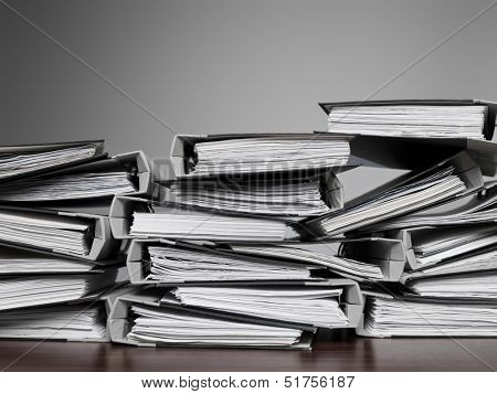 Overwelming number of files stacked on a desk