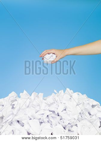 Hand with white paper on blue background