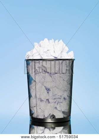 Full wastebasket on blue background